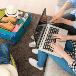 Personen auf einer Couch, die online nach Reiseangeboten schauen und gepackte Koffer vor sich liegen haben.