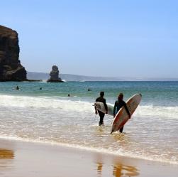 Zwei Surfer gehen mit Surfbrettern auf das Meer zu